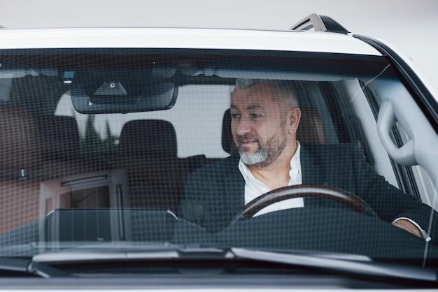 Vue De Face D'homme D'affaires Senior Dans Sa Nouvelle Voiture Moderne Testant De Nouvelles Fonctions Photo gratuit