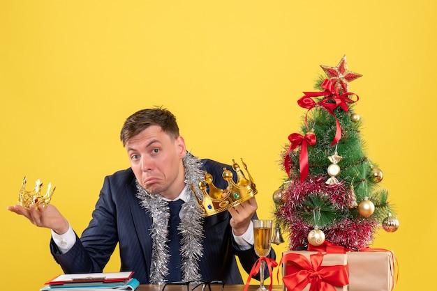 Vue De Face De L'homme D'affaires Tenant Des Couronnes Dans Les Deux Mains Assis à La Table Près De L'arbre De Noël Et Présente Sur Jaune Photo gratuit