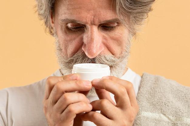 Vue De Face D'un Homme âgé Avec Une Crème Hydratante Qui Sent La Barbe Photo gratuit