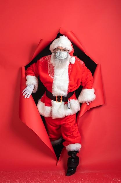 Vue De Face De L'homme En Costume De Père Noël Sortant De Papier Photo gratuit