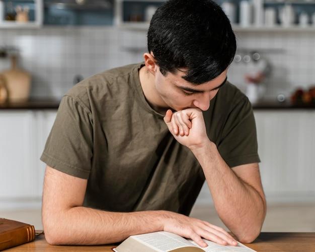 Vue De Face De L'homme Dans La Cuisine La Lecture De La Bible Photo gratuit