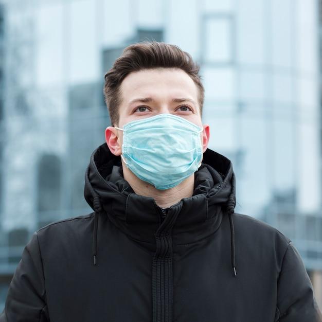 Vue De Face De L'homme Dans La Ville Avec Masque Médical Et Veste Photo gratuit