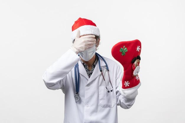 Vue De Face De L'homme Médecin Tenant De Grandes Chaussettes De Vacances Sur Le Virus Du Mur Blanc Vacances Covid Photo gratuit
