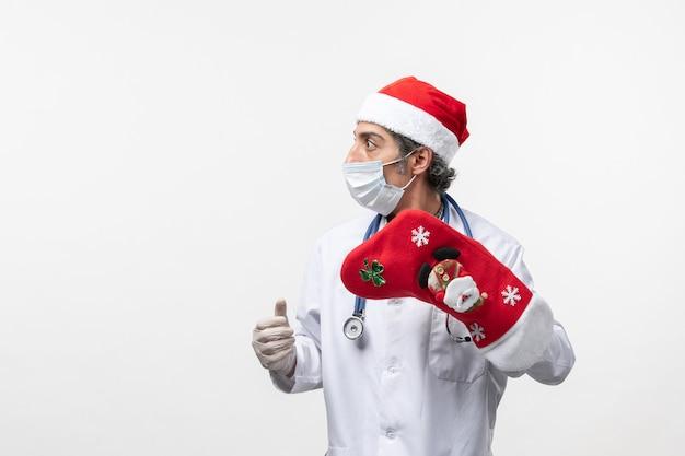 Vue De Face Homme Médecin Tenant Grosse Chaussette Rouge Sur Le Virus Mur Blanc Covid- Vacances Photo gratuit
