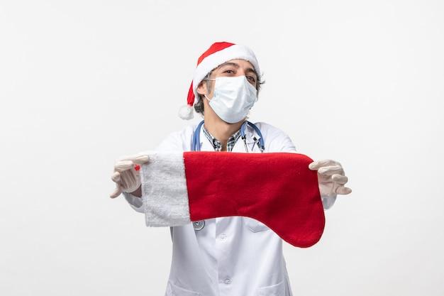 Vue De Face De L'homme Médecin Tenant Grosse Chaussette De Vacances Sur Mur Blanc Vacances Virus Covid Photo gratuit