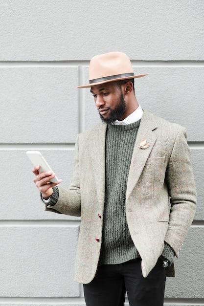 Vue De Face Homme Regardant Son Téléphone à L'extérieur Photo gratuit