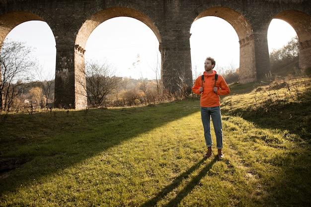 Vue De Face De L'homme Sur Un Road Trip Dans La Nature Posant à Côté De L'aqueduc Photo gratuit