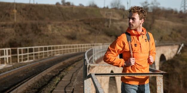 Vue De Face De L'homme Sur Un Road Trip Posant à Côté De Chemin De Fer Photo gratuit