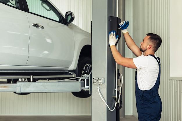 Vue de face, homme soulevant la voiture pour inspection Photo gratuit