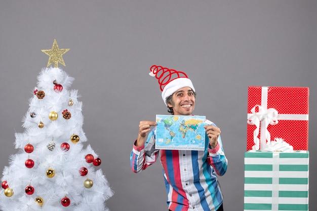 Vue De Face Homme Souriant Avec Bonnet De Noel Printemps En Spirale Tenant La Carte Avec Les Deux Mains Photo gratuit