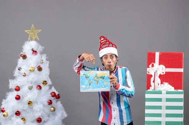 Vue De Face Homme Surpris Avec Bonnet De Noel Printemps En Spirale Et Chemise Rayée Montrant La Carte Près De L'arbre De Noël Blanc Et Présente Avec Copie Espace Photo gratuit