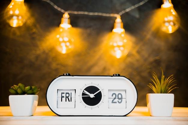 Vue de face de l'horloge et des ampoules avec table en bois Photo gratuit