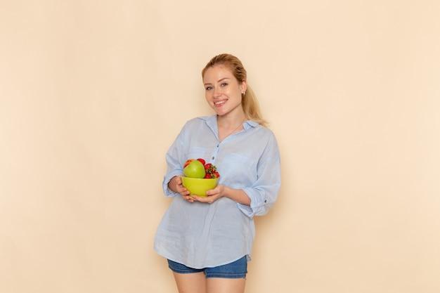 Vue De Face Jeune Belle Femme En Chemise Tenant La Plaque Avec Des Fruits Sur Le Mur Crème Fruits Mûrs Modèle Femme Pose Photo gratuit