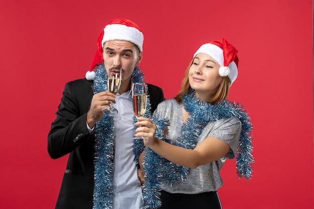 Vue De Face Jeune Couple Célébrant Le Nouvel An Sur Le Plancher Rouge Love Party Noël Photo gratuit