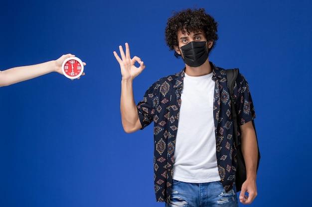 Vue De Face Jeune étudiant Masculin Portant Un Masque Noir Avec Sac à Dos Montrant Bien Signe Sur Fond Bleu. Photo gratuit