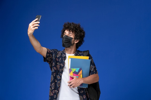 Vue De Face Jeune étudiant Masculin Portant Un Masque Noir Avec Sac à Dos Tenant Des Fichiers Et Prenant Selfie Sur Fond Bleu. Photo gratuit