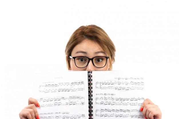 Une Vue De Face Jeune étudiante En T-shirt Rouge Jeans Noirs Portant Des écouteurs Noirs Holding Note Copybook Sur Le Blanc Photo gratuit