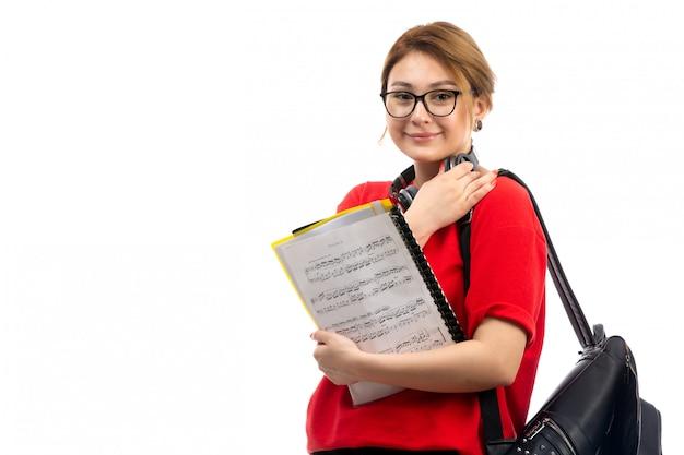 Une Vue De Face Jeune étudiante En T-shirt Rouge Jeans Noirs Portant Des écouteurs Noirs Tenant Un Cahier De Notes Souriant Sur Le Blanc Photo gratuit