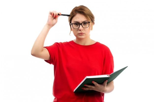 Une Vue De Face Jeune étudiante En T-shirt Rouge Tenant Un Cahier D'écrire Des Notes De Réflexion Sur Le Blanc Photo gratuit