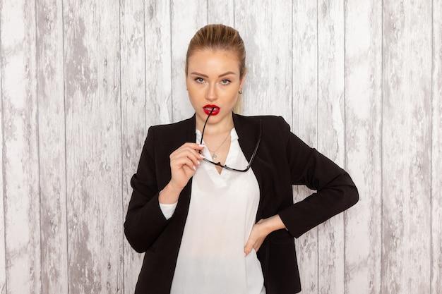 Vue De Face Jeune Femme D'affaires Dans Des Vêtements Stricts Veste Noire Avec Des Lunettes De Soleil Optiques Posant Sur Mur Blanc Travail Travail Bureau Femme D'affaires Photo gratuit