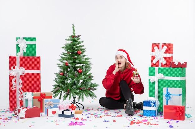 Vue De Face De La Jeune Femme Assise Autour Des Cadeaux De Vacances Tenant Quelque Chose Sur Le Mur Blanc Photo gratuit