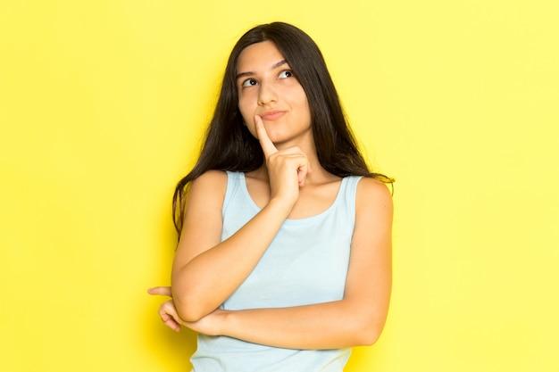 Une Vue De Face Jeune Femme En Chemise Bleue Posant Avec Expression De Pensée Photo gratuit
