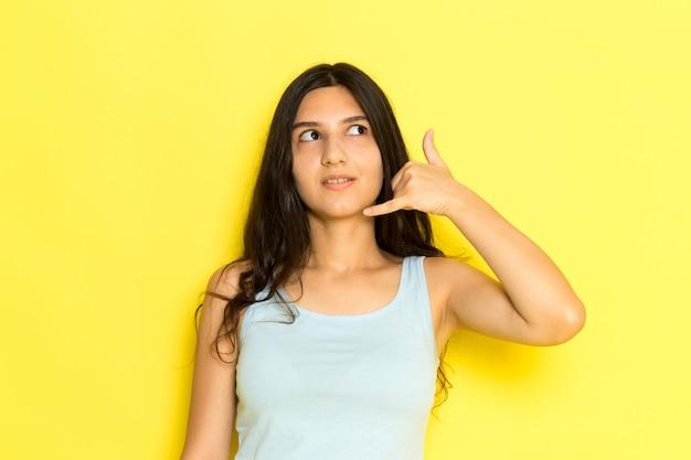 Une Vue De Face Jeune Femme En Chemise Bleue Posant Et Montrant L'indicatif D'appel Téléphonique Sur Le Fond Jaune Fille Pose Modèle Beauté Jeune Photo gratuit