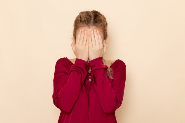 Vue De Face Jeune Femme En Chemise Rouge Couvrant Son Visage Sur La Crème De L'espace émotion Violence Photo Domestique Oclor Photo gratuit