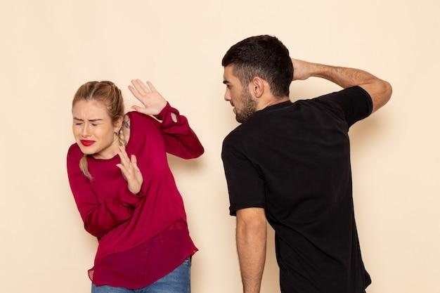 Vue De Face Jeune Femme En Chemise Rouge Souffre De Menaces Physiques Et De Violence Sur L'espace Crème Femme Tissu Photo Violence Domestique Photo gratuit
