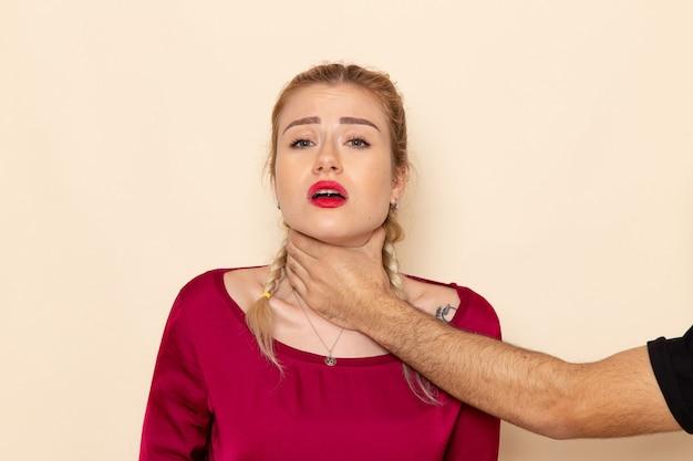 Vue De Face Jeune Femme En Chemise Rouge Souffre De Menaces Physiques Et De Violence Sur La Photo De Tissu Féminin Espace Crème Photo gratuit