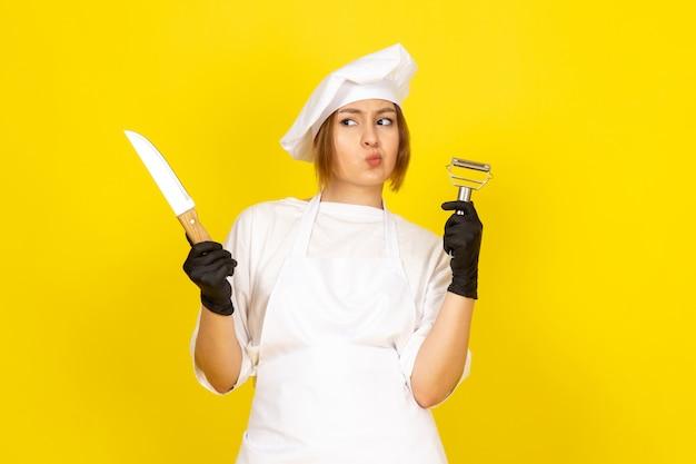 Une Vue De Face Jeune Femme Cuisinier En Costume De Cuisinier Blanc Et Bonnet Blanc En Gants Noirs Tenant Un Couteau Et Un Nettoyant Pour Légumes Sur Le Jaune Photo gratuit