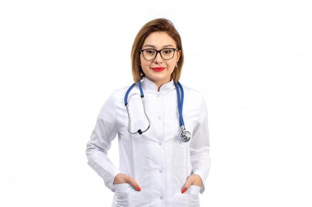 Une Vue De Face Jeune Femme Médecin En Costume Médical Blanc Avec Stéthoscope Souriant Sur Le Blanc Photo gratuit