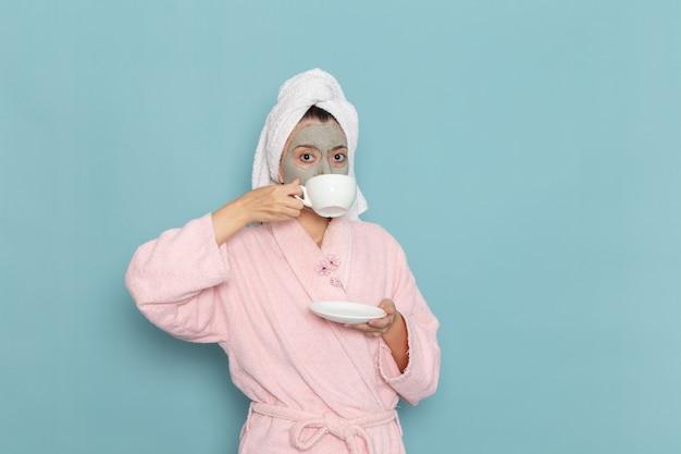Vue De Face Jeune Femme En Peignoir Rose Après La Douche, Boire Du Café Sur Le Mur Bleu Clair Beauté Eau Propre Douche Selfcare Photo gratuit