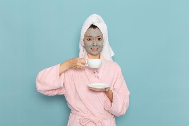 Vue De Face Jeune Femme En Peignoir Rose Après La Douche, Boire Du Café Avec Sourire Sur Le Mur Bleu Nettoyage Beauté Eau Propre Douche Crème Auto-soin Photo gratuit