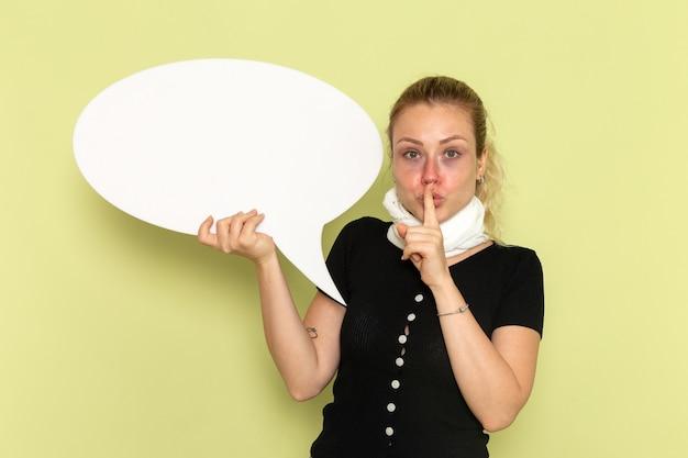 Vue De Face Jeune Femme Se Sentant Très Malade Et Malade Tenant Un énorme Panneau Blanc Demandant De Se Taire Sur Le Mur Vert Maladie Médecine Santé Maladie Photo gratuit