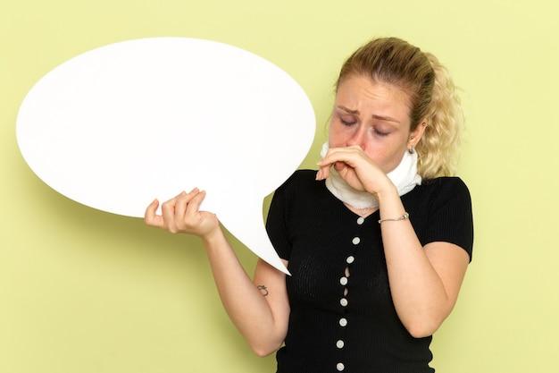 Vue De Face Jeune Femme Se Sentant Très Malade Et Malade Tenant Un énorme Panneau Blanc Nettoyant Son Nez Sur Le Mur Vert Maladie Médecine Maladie Santé Photo gratuit