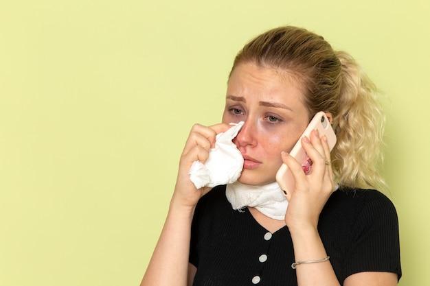 Vue De Face Jeune Femme Se Sentir Très Malade Et Malade De Parler Au Téléphone Sur Le Mur Vert Maladie Médecine Maladie Photo gratuit