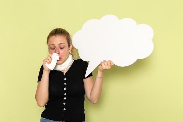 Vue De Face Jeune Femme Se Sentir Très Malade Et Malade Tenant Un énorme Panneau Blanc Sur Le Mur Vert Fille Maladie Médecine Santé Maladie Photo gratuit