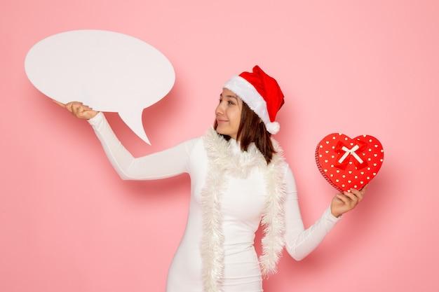 Vue De Face Jeune Femme Tenant Grand Panneau Blanc Et Présent Sur La Couleur Du Mur Rose Photo gratuit