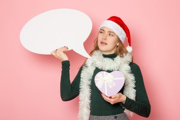 Vue De Face Jeune Femme Tenant Grand Panneau Blanc Et Présent Sur Le Modèle De Mur Rose Noël Nouvel An Vacances Couleur émotion Photo gratuit