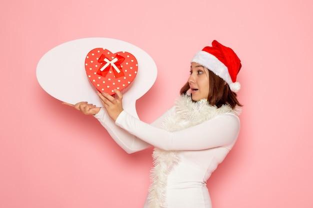 Vue De Face Jeune Femme Tenant Grand Panneau Blanc Et Présent Sur Le Mur Rose Couleur émotion Vacances Nouvel An De Noël Photo gratuit