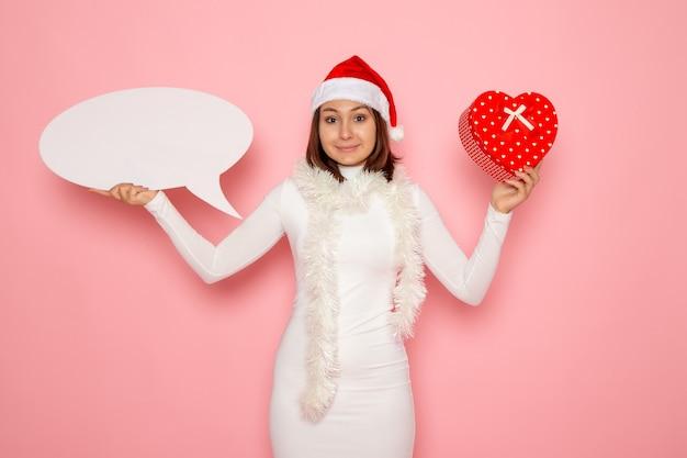Vue De Face Jeune Femme Tenant Grand Panneau Blanc Et Présent Sur Le Mur Rose Couleur Neige Noël Nouvel An Vacances D'émotion Photo gratuit