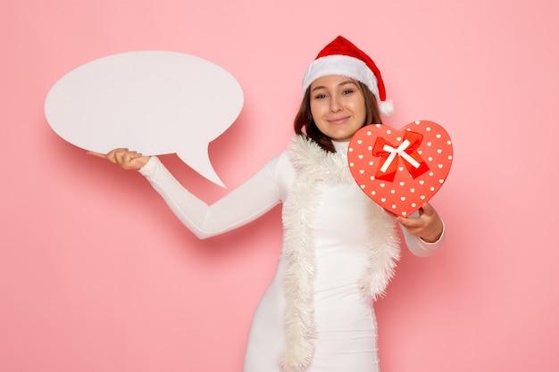 Vue De Face Jeune Femme Tenant Grand Panneau Blanc Et Présent Sur Le Mur Rose Couleur Noël Nouvel An Vacances D'émotion Photo gratuit