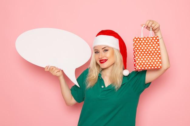 Vue De Face Jeune Femme Tenant Grand Panneau Blanc Et Présent Sur Le Mur Rose Photo Couleur Neige Nouvel An Vacances Femme Photo gratuit