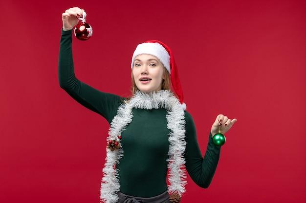 Vue De Face Jeune Femme Tenant Des Jouets D'arbre De Noël Sur Le Fond Rouge Photo gratuit