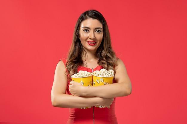 Vue De Face Jeune Femme Tenant Des Paquets De Pop-corn Et Souriant Sur La Surface Rouge Photo gratuit