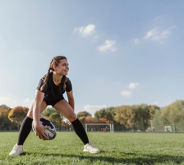 Vue de face jeune fille tenant un ballon de rugby avec espace de copie Photo gratuit