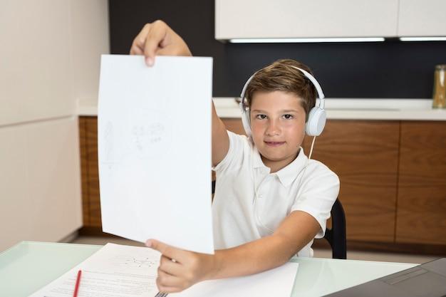Vue De Face Jeune Garçon Tenant Du Papier à La Maison Photo gratuit
