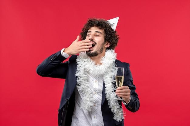 Vue De Face Jeune Homme Célébrant Une Autre Année Sur Le Mur Rouge Noël Vacances Humaines Photo gratuit