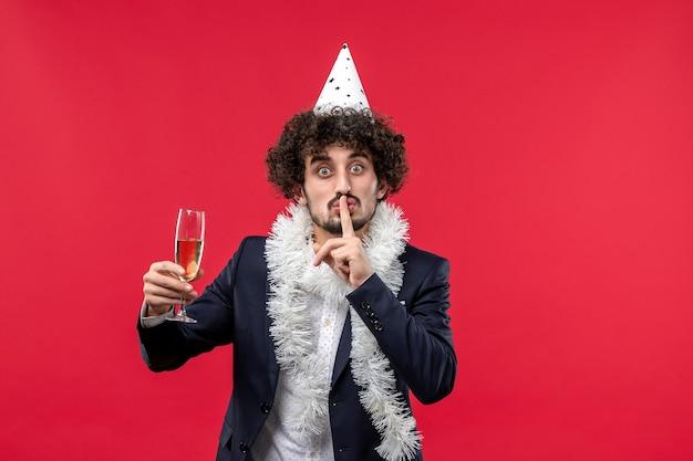 Vue De Face Jeune Homme Célébrant Le Nouvel An à Venir Sur Le Mur Rouge Vacances Noël Humain Photo gratuit